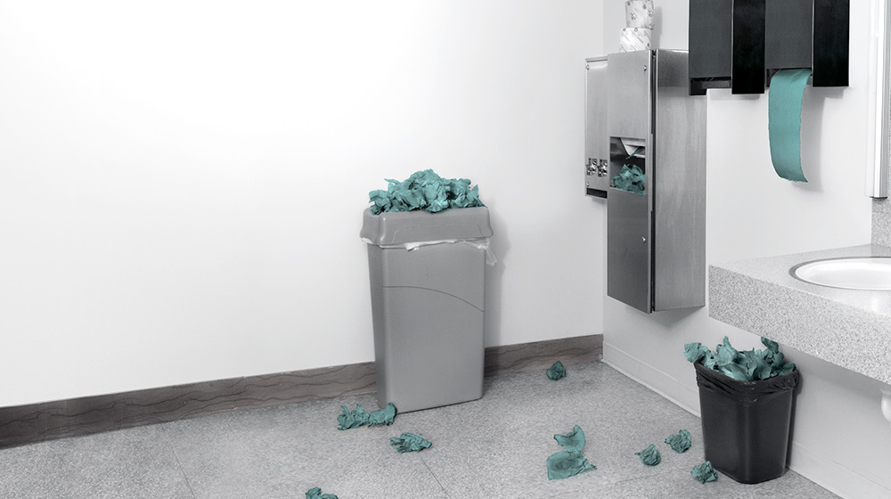 Washroom with paper towels on the floor and in overflowing bins