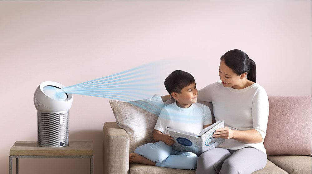 A woman reads to her son, next to a Dyson personal purifier fan