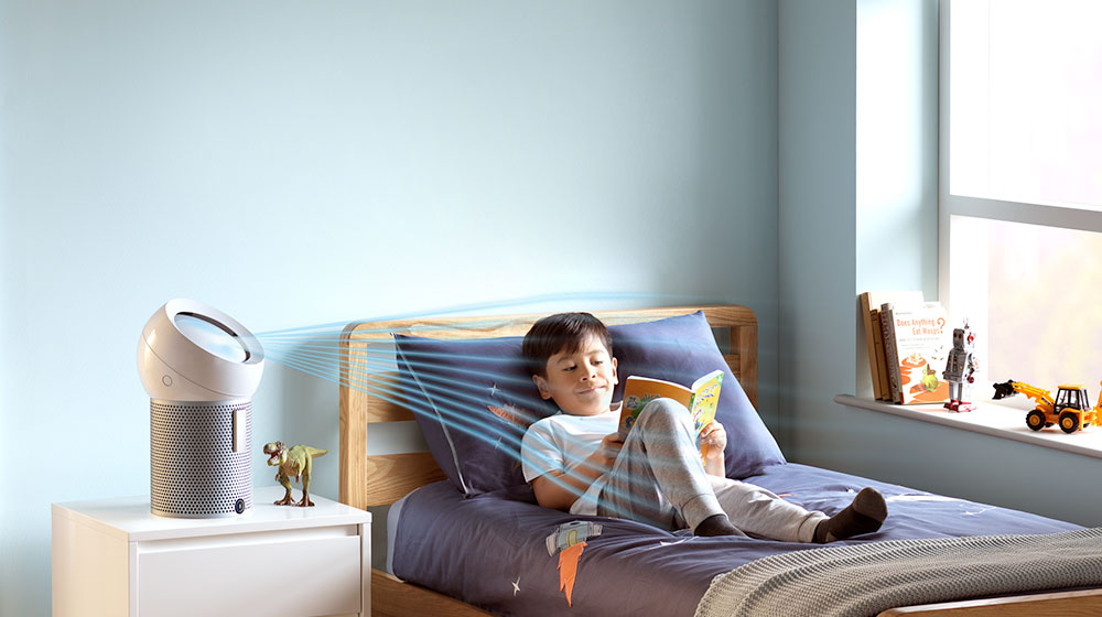 A boy reads on his bed, while a Dyson personal purifier fan projects cooling airflow at him